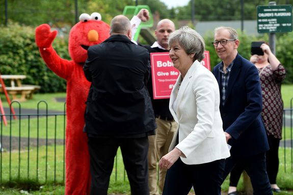 Theresa May and husband Philip are greeted by Elmo at their polling station.