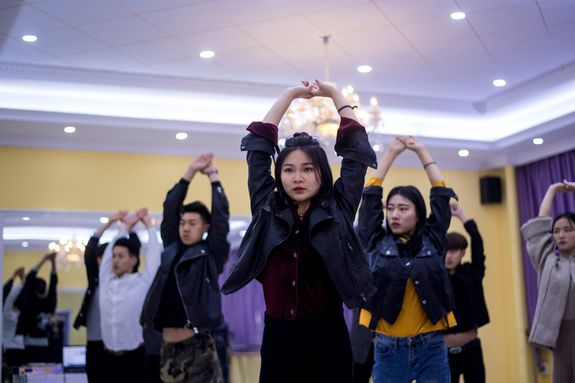 This picture taken on March 14, 2017 shows Wang Xin (C) attending a dance class at the Yiwu Industrial & Commercial College in Yiwu, east China's Zhejiang Province.  Hordes of Chinese millennials are speaking directly to the country's 700 million smartphone users, streaming their lives to lucrative effect, fronting brands and launching businesses. They are known as